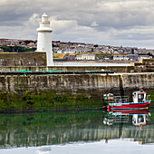 'Fishing boat moored in a tranquil harbour with a white lighthouse and cityscape; Macduff, Aberdeenshire, Scotland'