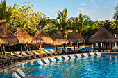 'Swimming pool and lounge chairs at a resort on the Caribbean; Playa del Carmen, Quintana Roo, Mexico'
