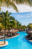 'Swimming pool and tourists sunbathing at a resort on the Caribbean; Playa del Carmen, Quintana Roo, Mexico'