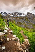Man hikes the Reed Lakes Trail in Archangel Valley, Talkeetna Mountains, Southcentral Alaska, summer