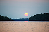 'A red sun setting over the forest with a lake reflecting the pink glow; Manitoba, Canada'
