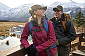 Backpacking couple looks out over the Eagle River Valley and Chugach Mountains from a viewing deck on the Rodak Nature Trail in Chugach State Park near the Eagle River Nature Center in Southcentral Alaska