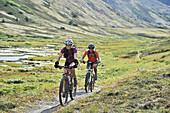 Women ride full suspension mountain bikes on the Resurrection Pass Trail in the Chugach National Forest, Kenai Peninsula, Southcentral Alaska