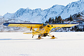 Piper PA-18 Super Cub on skis with the Kenai Mountains in the background, Southcentral Alaska.