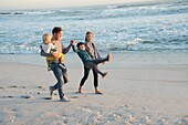 Happy young family having fun on the beach at sunset