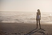 Rear view of a woman standing on the beach