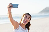 Playful young woman taking selfie with smartphone on the beach