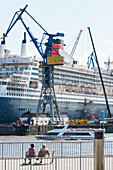 A pair sitting at the landing stages in front of the dry dock of the shipyard Blohm and Voss where the cruise ship QE2 is being overhault, Hamburg, Germany