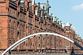 The Kehrwiedersteg bridge over the Kehrwiederfleet in front of the historical warehouse district Speicherstadt, Hamburg, Germany