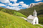 'Old woman outside the church; on the background Odle di Eores. Trentino Alto Adige, Italy.'