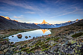 Hikers admire Matterhorn reflected in Lake Stellisee at dawn Zermatt Canton of Valais Switzerland Europe