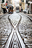 The steel rails on a rainy day with the typical trams leading to Bairro Alto district Lisbon Portugal Europe