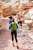 Women running in canyon wearing backpacks