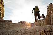 Woman running in canyon wearing backpack