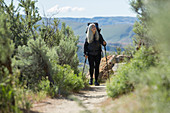 Older Caucasian woman hiking with backpack on path