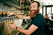 Smiling Caucasian bartender pouring beer