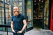 Caucasian man with beard smiling on sidewalk