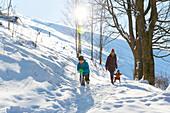 Junge Familie im Schnee, Neuschnee, Schneeball, Berg, Winterwald, Junge, 5 Jahre, Mama, Tochter auf Schlitten, 2 jahre, Harz, MR, Sankt Andreasberg, Niedersachen, Deutschland