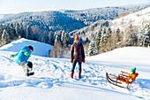 Junge Familie im Schnee, Junge springt in den Schnee, verschneiter Wald, Junge, 5 Jahre, Mama, Mutter, Tochter auf Schlitten, 2 Jahre, Harz, MR, Sankt Andreasberg, Niedersachen, Deutschland
