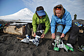 Skiers gear up on the beach of Augustine Island in Cook Inlet, Alaska. The men and women skiers prepare for an ascent of Mt Augustine, the 4,025-foot high active volcano that dominates the island.
