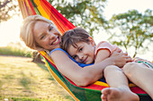 Mother and son relaxing in hammock together