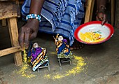 Benin, West Africa, Bopa, miss hounyoga blessing the carved wooden figures made to house the soul of her dead twins.