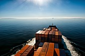 Container vessel crossing the Baltic Sea at sunset, Europe.