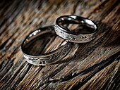 Two white gold wedding rings with Celtic design on rustic wood background, artistic still life.