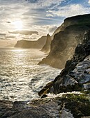 The west coast near Traelanipa with waterfall Bosdalafossur at sunset. The island Vagar, part of the Faroe Islands in the North Atlantic. Europe, Northern Europe, Denmark, Faroe Islands.