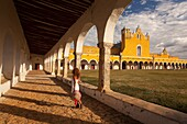 Woman posing at Izamal convent, Monastery-Convent Of San Antonio De Padua, Izamal, Yucatan, Yucatan Province, Mexico, Central America.