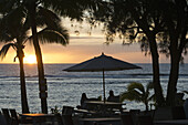 Rarotonga Island. Cook Island. Polynesia. South Pacific Ocean. Sunset on the beach in Hotel Crown Beach Resort & Spa. Lit. Tourists taking photos. Parasols. The Crown Beach Resort comprises of 22 villas nestled in four and a half acres of tropical garden,