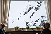 Guests looking through a window at a male skier jumping down a cliff, Andermatt, Uri, Switzerland
