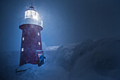 Young male skier standing at a lighthouse during a snowstorm at night, Andermatt, Uri, Switzerland
