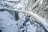 Snow-covered stone bridge over an iced river, Andermatt, Uri, Switzerland