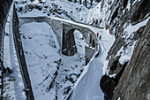 Two young male skier walking over a snow-covered stone bridge, Andermatt, Uri, Switzerland