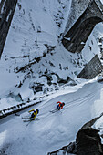 Two young male skier riding on a snow-covered street at a stone bridge, Andermatt, Uri, Switzerland