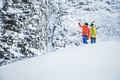 Two young skiers planing their next line in the mountains, Andermatt, Uri, Switzerland