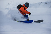 Young male skier riding through deep powder snow apart the slope, Andermatt, Uri, Switzerland
