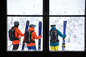 Three young male skiers standing outside of a cottage in the mountains, Andermatt, Uri, Switzerland