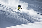Young male skier jumping in the deep powder snow, Andermatt, Uri, Switzerland
