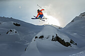 Young male skier jumping over a cliff apart the slope, Andermatt, Uri, Switzerland
