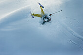 Young male skier falling into the deep powder snow apart the slopes, Andermatt, Uri, Switzerland
