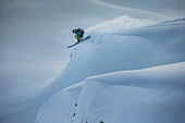 Young male skier jumping in the deep powder snow apart the slopes, Andermatt, Uri, Switzerland