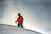 Young male skier standing in the deep powder snow apart the slopes in the mountains, Andermatt, Uri, Switzerland