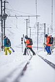 Three young male skiers going over railroad tracks, Andermatt, Uri, Switzerland