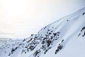 Young male skier riding through deep powder snow apart the slope, Andermatt, Uri, Switzerland