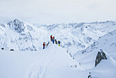 Four young male skiers standing at the top of a mountain, Andermatt, Uri, Switzerland