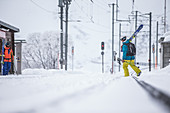 Two young male skiers at a snow-covered litte rail station, Andermatt, Uri, Switzerland