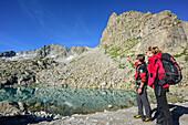 Mann und Frau stehen an Bergsee und blicken auf Bergkulisse, Adamello-Presanella-Gruppe, Trentino, Italien