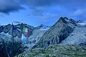 Im Wind wehende Flaggen stehen vor Bergkulisse mit Crozzon di Lares und Lobbia Alta, Rifugio Madron, Adamello-Presanella-Gruppe, Trentino, Italien